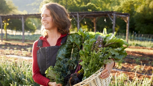 women smiling outside with basket of vegetables