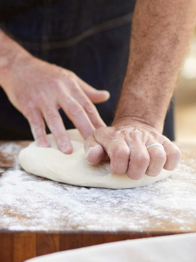 chef kneading pizza dough