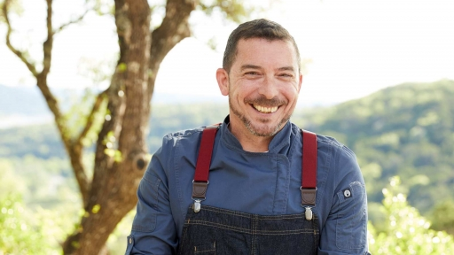 man with big smile outside wearing overalls