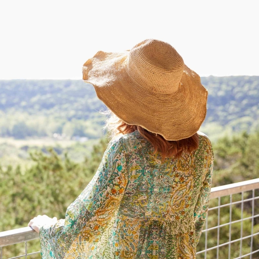 Woman in hat enjoys scenic overlook at Miraval Austin.