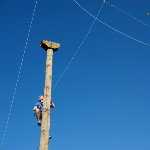 man climbing ropes course at miraval austin