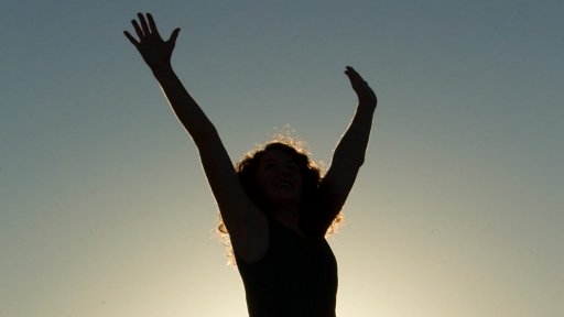 shadowed picture of women raising hands in the air