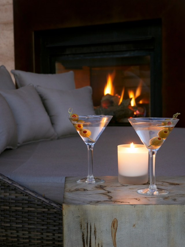 two martinis sitting by a lit fireplace