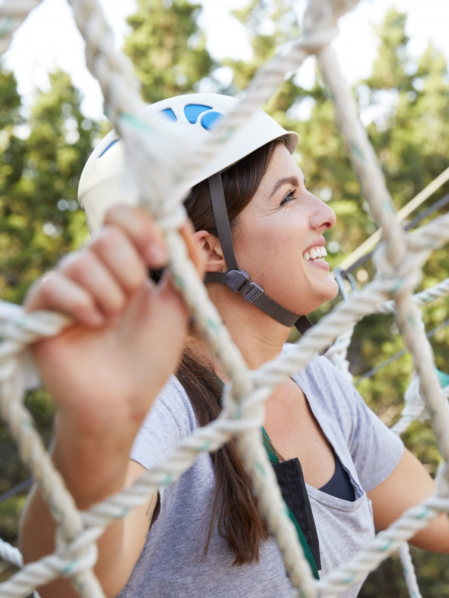 woman happily climbing ropes course at miraval austin
