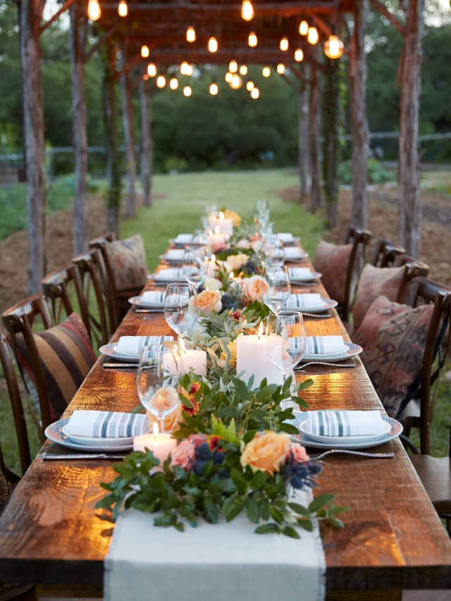 large wooden dinner table underneath outside lighting