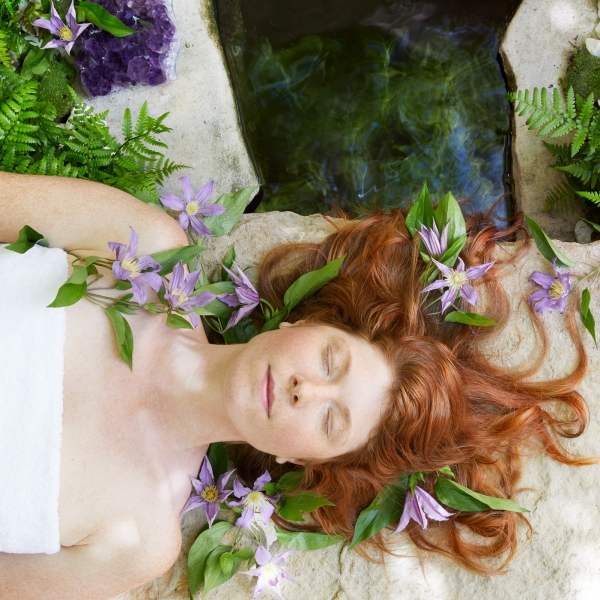 red haired woman laying on back with eyes closed