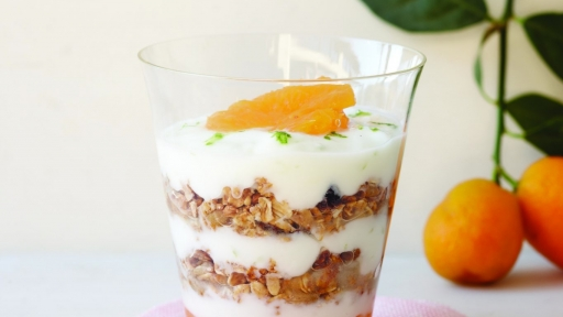 granola and yogurt parfait topped with orange piece