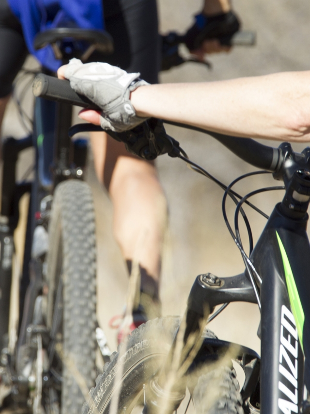 hands with biking gloves grasping bike handles