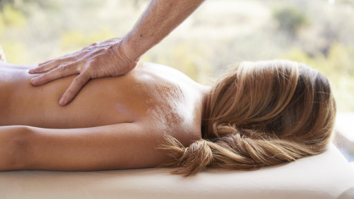 blonde woman receiving back massage at miraval austin