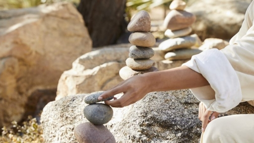 woman's hand stacking stone