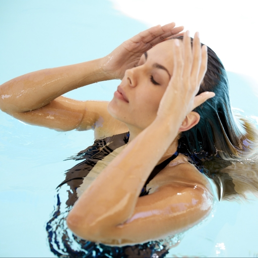 woman with eyes closed pulling hair back in pool