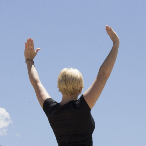 blonde women with short hair raising hands in the air