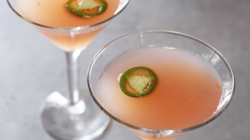 two peach martinis garnished with jalapeno