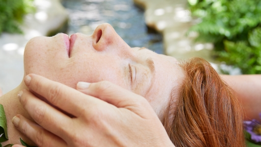 Woman enjoys facial massage outdoors at Miraval Austin.