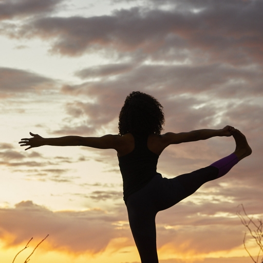 Woman holds own foot during yoga pose in front of sunset at Miraval Austin.