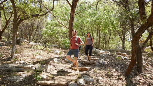 Couple enjoys hiking in the woods at Miraval Austin Resort.