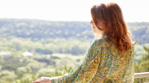 Woman with red hair enjoys the view from scenic overlook at Miraval Austin.