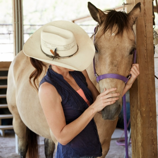 woman wearing cowboy hat petting nose of tan horse