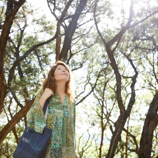 Woman looks up to the sky in the woods at Miraval Austin Resort.
