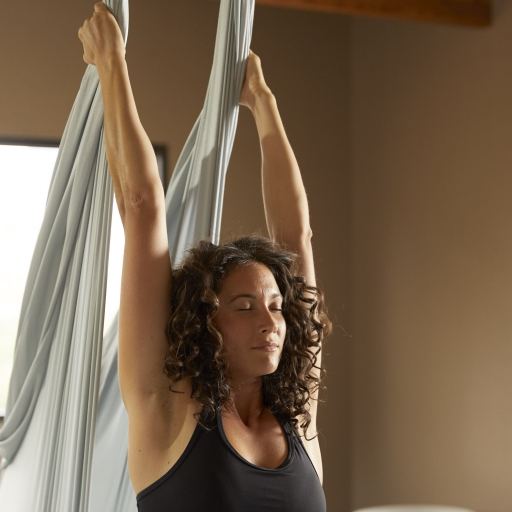 woman with eyes closed stretching arms