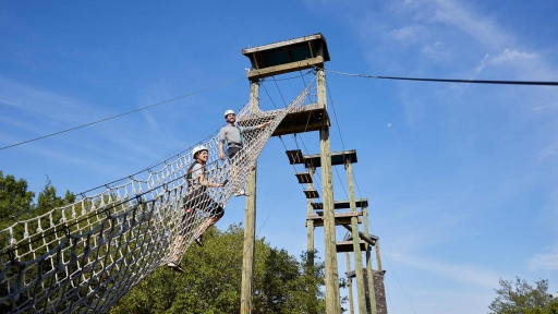 couple climbing the ropes course at miraval austin resort in texas