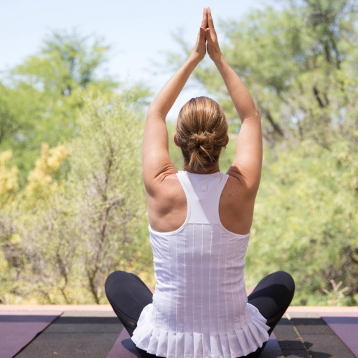 Woman does a yoga pose outdoors at Miraval Austin.