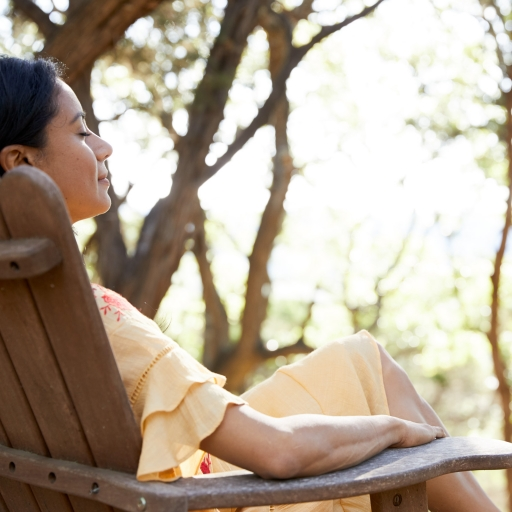 woman with soft smile relaxing in wooden chair