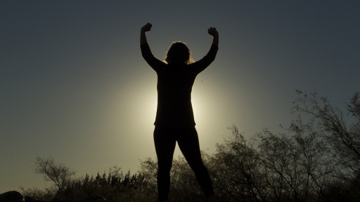 shadowed picture of woman in front of sun stretching