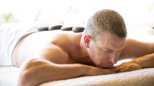 man laying with hot stones on his back