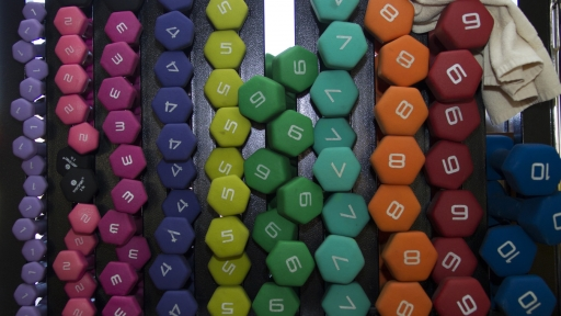 colorful arrangement of workout weights on rack