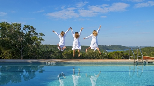 Group of friends jumping in to the pool at Miraval Austin Resort & Spa