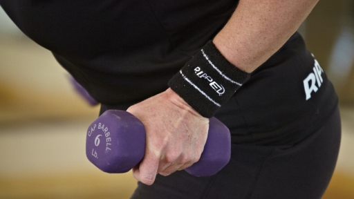 hand holding purple six pound dumbbell