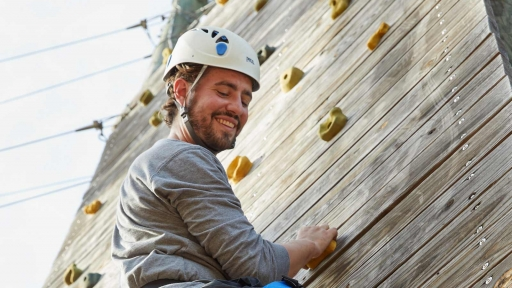 man looking down smiling while climbing a rock wall