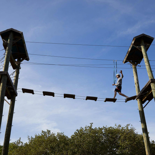Guest walks through elevated challenge course at Miraval Austin.